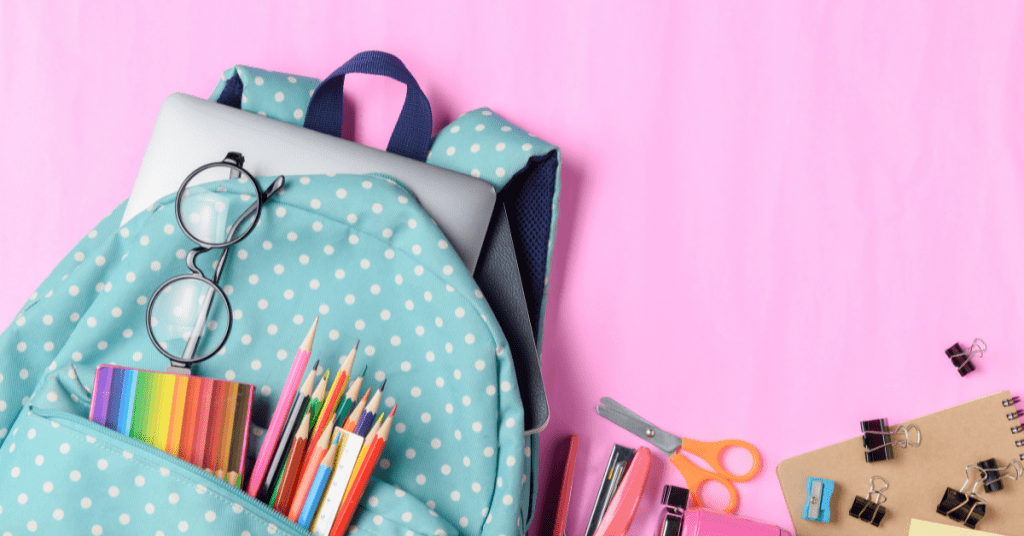 back to school items in book bag. Colored pencils, scissors, and pens on a pink background